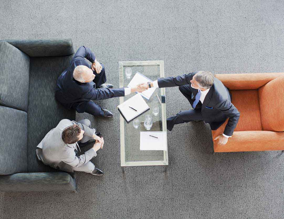 Men Shaking Hands over Coffee Table with Documents